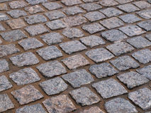 Old pavement. Old road pavement of the small rough granite tiles stock image