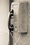 Old payphone closeup and located outdoor on a wall. The big old payphone of sepia color a closeup and located outdoor on a wall royalty free stock images