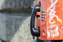 Old payphone on a stone wall. The old red payphone with a black receiver is fixed on a stone wall with a blank space for the text stock photos