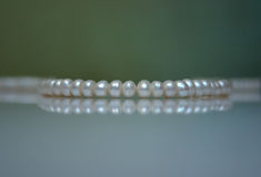 Old pearl beads. On a greenish background. Shallow DOF Royalty Free Stock Photos