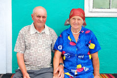 Old peasant couple. With their old house in the background royalty free stock image