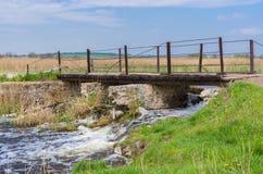 Old pedestrian bridge over small Ukrainian river Kilchen Stock Photos