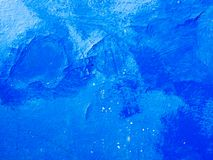 Old, peeling blue paint on the wall is painted on top of a darker blue paint. stock image