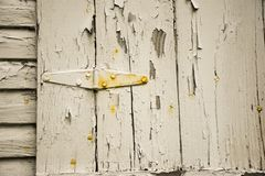 OLD PEELING CRACKED WHITE PAINT ON WOOD SIDING. The siding of a house shows the peeling and cracked white paint that shows the need for a new coat royalty free stock photo