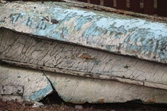 Old peeling paint on the sides of the broken boat. Stock Photo
