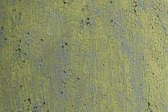 Old peeling yellow paint on gray. stock image