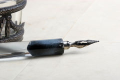 Old pen. Old calligraphy pen on paper with copy space royalty free stock image