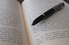 An old pen lying on a book !. An old ink pen lying on an italian book Stock Photo