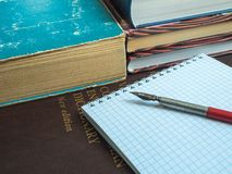 The old fountain pen lies on an open notebook next to the books royalty free stock images