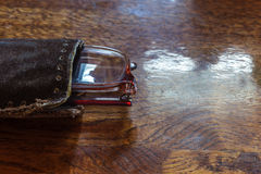 Old pensioner glasses on lacquered wooden surface. Blurred visio Stock Photo