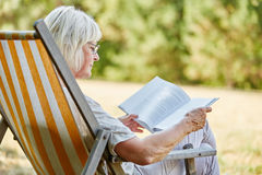 Old pensioner reading in summer. Old pensioner reading a book in summer in the nature Stock Photo