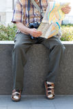 Old pensioner in socks and sandals searching destination on map Stock Photography