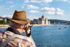 Old pensioner tourist shooting Parliament building at Budapest Stock Image