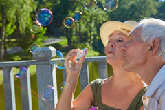 Old people with bubble blower. Couple of seniors royalty free stock photography