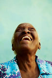 Portrait of funny elderly black woman smiling and laughing. Old people and emotions, portrait of bizarre senior african american lady laughing with head tilted royalty free stock photography