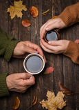Old people hands. Closeup. The senior people hand holding a cup. Of coffee on the wood table covered with autumn leaves. Old age concept Stock Images