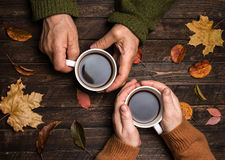 Old people hands. Closeup. The senior people hand holding a cup. Of coffee on the wood table covered with autumn leaves. Old age concept Royalty Free Stock Image