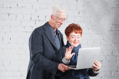 Old people hold a laptop and communicate through the Internet. Happy smiling grandpa grandma couple standing cuddling. Together isolated on white brick Stock Images