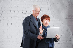 Old people hold a laptop and communicate through the Internet. Happy smiling grandpa grandma couple standing cuddling. Together isolated on white brick Royalty Free Stock Image