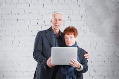 Old people hold a laptop and communicate through the Internet. Happy smiling grandpa grandma couple standing cuddling. Together isolated on white brick Royalty Free Stock Photo