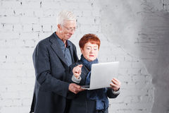 Old people hold a laptop and communicate through the Internet. Happy smiling grandpa grandma couple standing cuddling. Together isolated on white brick Stock Image
