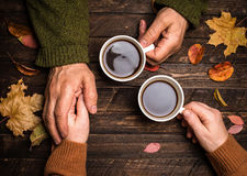 Old people holding hands. Closeup. The senior people hand holding a cup of coffee on wooden rustic table covered with autumn
