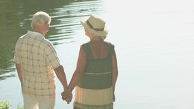 Old people holding hands. Couple of seniors standing near water in sunny day. Love that lasts a lifetime stock video footage