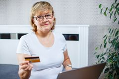 Old people and modern technology concept. Portrait of a 50s mature woman hand holding credit card. Using online internet payment at home. Indoor senior people stock image