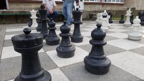 Old men playing giant chess. Old people outdoors in a park playing chess Stock Photo