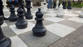 Old men playing giant chess. Old people outdoors in a park playing chess Stock Photography