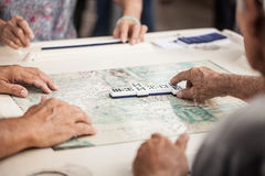 Old people playing dominoes. A group of elderly people playing dominoes Royalty Free Stock Image