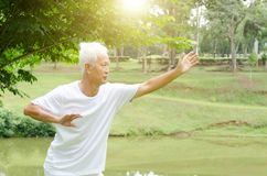 Old people practicing qigong in the park. Portrait of healthy white hair Asian senior man practicing martial arts at outdoor park in morning Stock Photography
