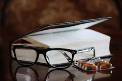 Old people reading. A book and glasses on it, together with some pills royalty free stock images