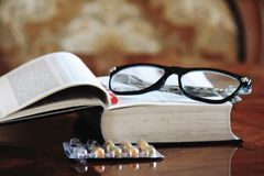 Old people reading. A book and glasses on it, together with some pills stock photos