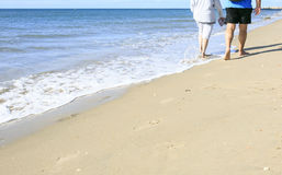 Old people taking a walk on the beach.  Royalty Free Stock Photos