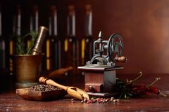 Old pepper mill with cooking utensils. Bottles of olive oil, spices and rosemary on a brown background royalty free stock photos