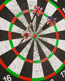 Old perforation dartboard with flags on darts. Focus on center of target Royalty Free Stock Photography