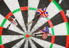 Old perforation dartboard with flags on darts. Focus on flag Stock Images