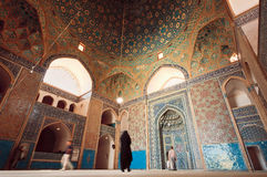 Old Persian mosque and people praying inside of tiled hall Royalty Free Stock Images