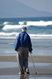 An Old Person on the Beach. An elderly person strolls down the beach alone Stock Image