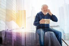 Old person crying while looking at the photo in his hands Stock Photo