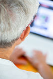 Old person in glasses busy working with a laptop Royalty Free Stock Image