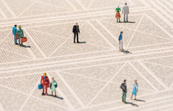 Old person miniature - Lonely man standing lost in the crowd royalty free stock photo