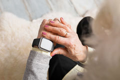 Old person using smart watch. On wrist Royalty Free Stock Photography