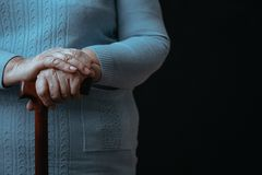 Old person with walking stick. Black background, close up Royalty Free Stock Photos