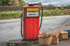 Old petrol station with vintage fuel pump and country side attributes.  Stock Photo