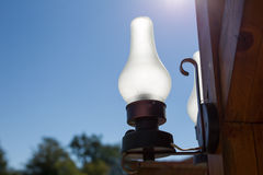 Old petroleum lamp. A old petroleum lamp on blue sky in background stock photos
