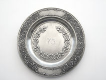 Old pewter dish with number 75 and oak and lily ornament. Old pewter dish (plate) with number 75 and oak and lily ornament Royalty Free Stock Photos