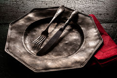 Old pewter plate with eating utensils Royalty Free Stock Photos