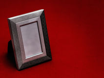 Old pewter style picture frame, empty, on red. Loss etc. Vintage. Dark, somewhat Gothic style image. Unbranded frame Royalty Free Stock Photography